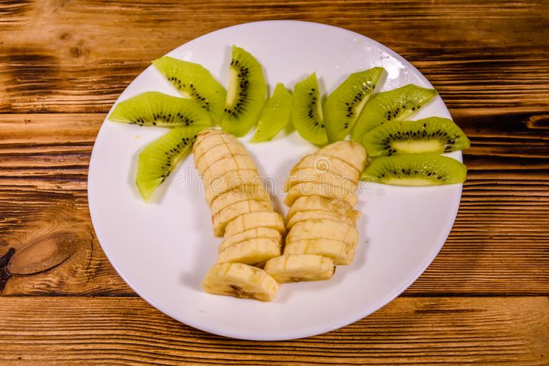 Healthy fruit dessert for children with kiwi and bananas shaped as a palm tree on white plate. Healthy fruit dessert for children with kiwi and bananas shaped as stock image