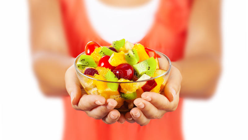 Healthy fruit salad. Healthy mix fruit salad, closeup on fresh summer dessert, woman holds lunch bowl, selective focus on female hands, eating girl shallow dof royalty free stock photography