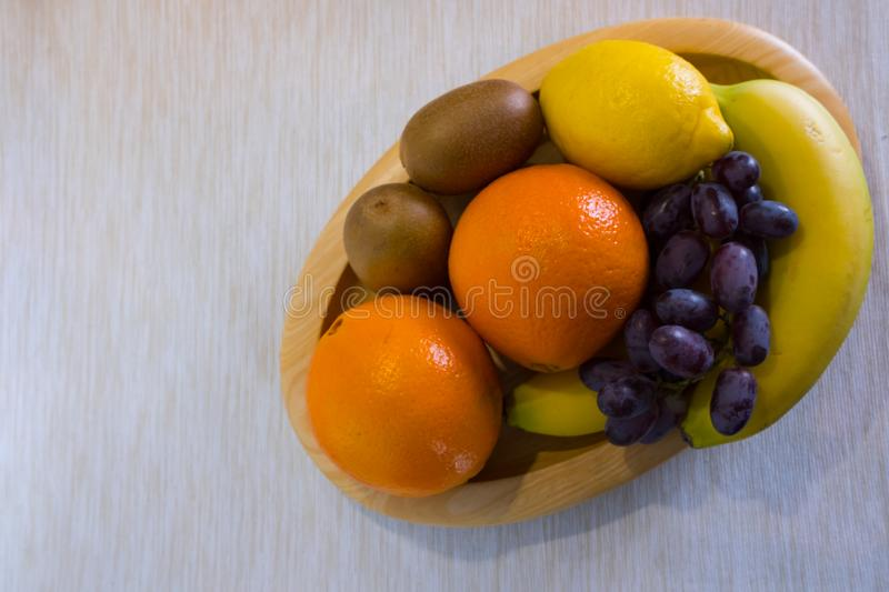 Healthy fruits in a wooden bowl stock photo