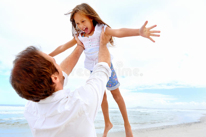 Healthy fun family. Healthy father and daughter playing together at the beach carefree happy fun smiling lifestyle