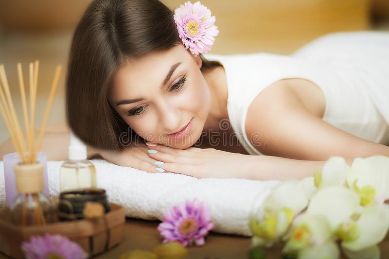 A healthy girl relaxing on the massage table. Before the procedure in the spa. Masseur goes to massage his back. Body care. Skin c. Young beautiful woman on the royalty free stock photos