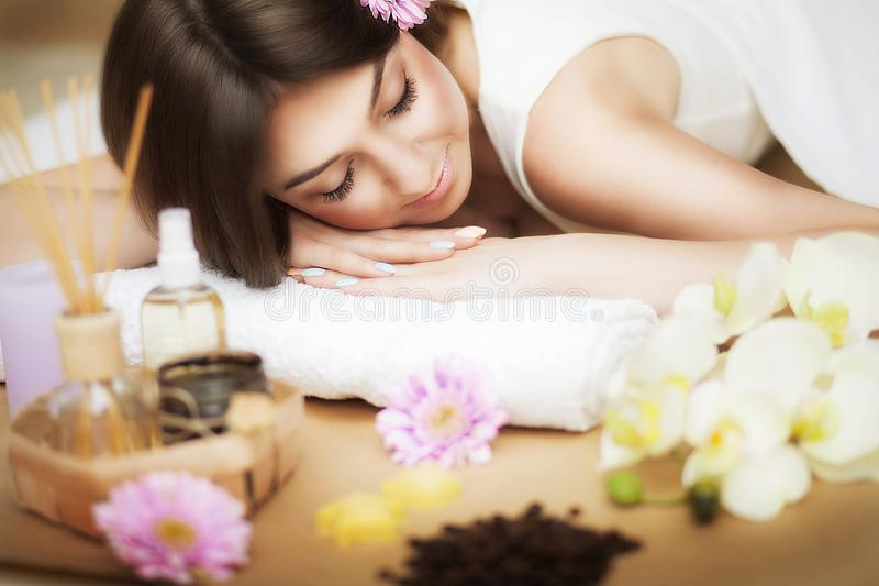 A healthy girl relaxing on the massage table. Before the procedure in the spa. Masseur goes to massage his back. Body care. Skin c. Young beautiful woman on the royalty free stock photography