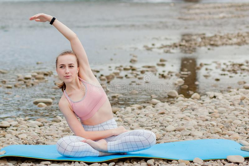 Healthy girl relaxing while meditating and doing yoga exercise in the beautiful nature on the bank of the river stock photography