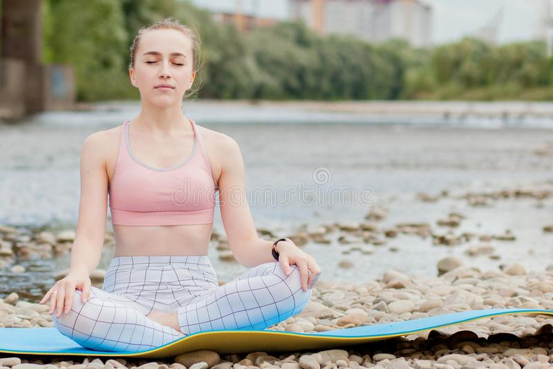 Healthy girl relaxing while meditating and doing yoga exercise in the beautiful nature on the bank of the river.  royalty free stock photo