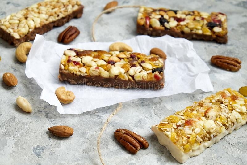 Healthy granola bars with nuts, seeds and dried fruits on the gray texture table, with copy space. Healthy breakfast on window sill homemade granola with nuts royalty free stock photos