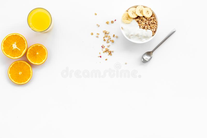 Healthy granola and orange juice for colorful breakfast on white background top view mock-up. Healthy granola in bowl and orange juice in glass for colorful royalty free stock photos
