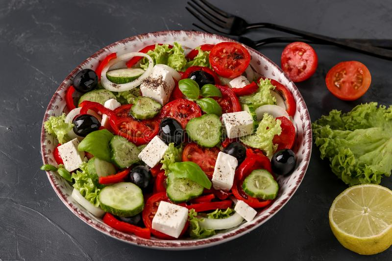 Healthy Greek salad of green lettuce, cherry tomato, onion, pepper, feta cheese, black olives, basil, cucumbers, with olive oil stock photo