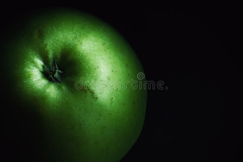Healthy Green Apple. Details of one green apple on dark background royalty free stock photography
