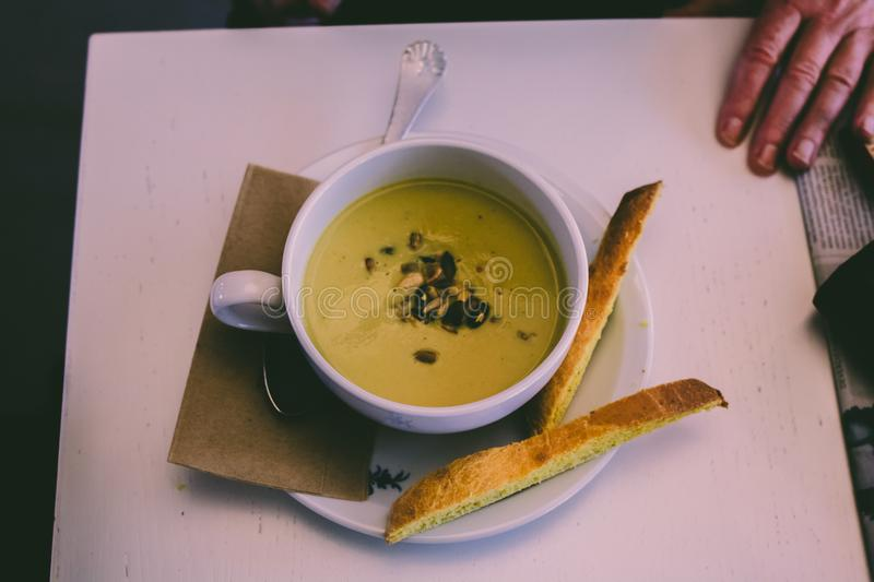 Healthy green autumn vegetable soup with breadsticks on table wi stock photo