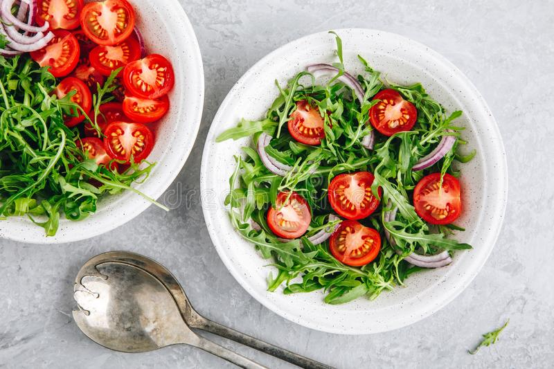 Healthy Green Fresh Arugula Salad Bowl with Tomatoes and Red Onions. Top view stock photography