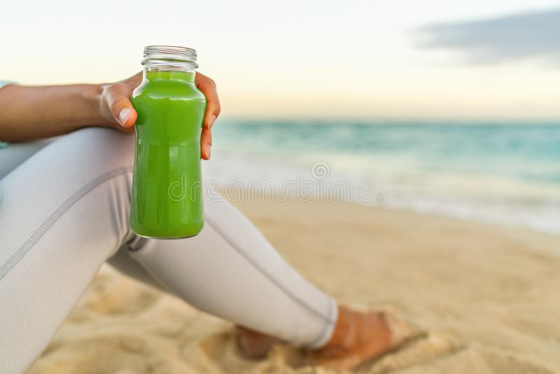 Healthy green juice detox smoothie drink beach woman. Girl holding glass bottle of cold pressed vegetable, juicing trend for stock photography