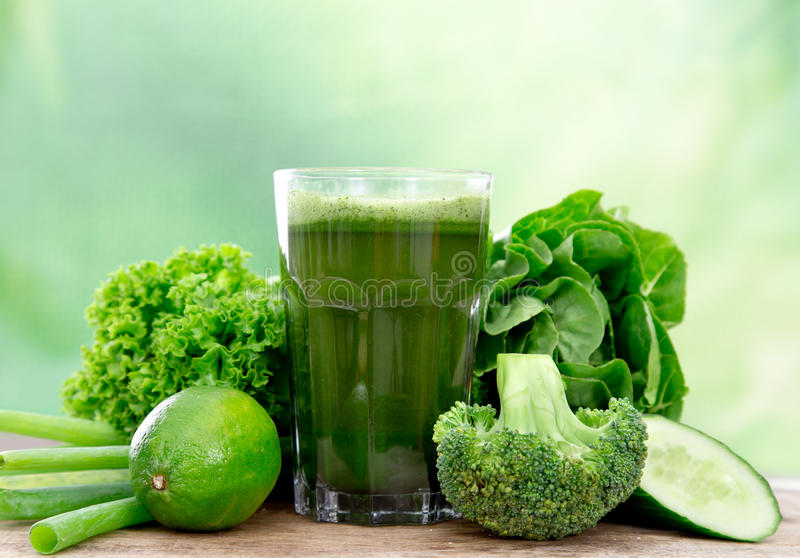 Healthy green juice. Healthy green vegetable juice on wooden table royalty free stock photo