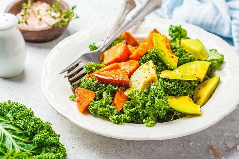 Healthy green kale salad with avocado and baked sweet potatoes. Plant based diet concept, detox food royalty free stock images
