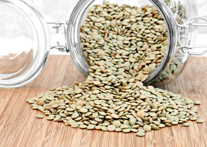 Healthy green lentil beans spilling from a jar. stock image
