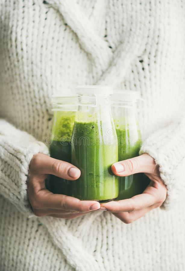 Healthy green smoothie or juice in bottles in female hands. Winter seasonal smoothie drink detox. Female in light knitted sweater holding bottles of green stock photos