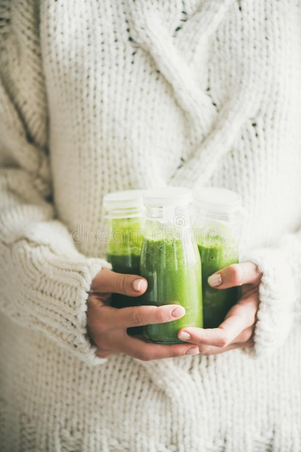 Healthy green smoothie or juice in bottles in woman`s hands. Winter seasonal smoothie drink detox. Female in knitted sweater holding bottles of green smoothie or royalty free stock image