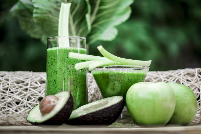 Healthy green smoothies. Green smoothies with organic fresh fruits and vegetables royalty free stock images