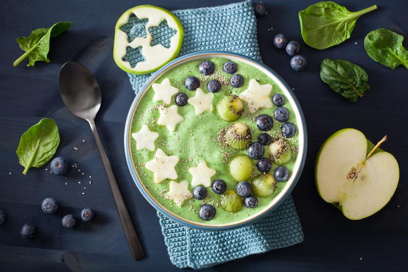 Healthy green spinach smoothie bowl with blueberry, apple stars, kiwi, chia seed royalty free stock photography