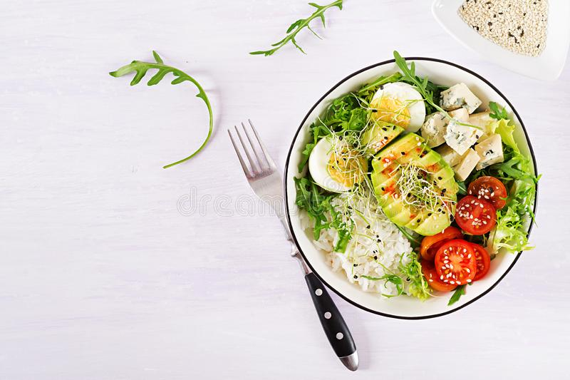 Healthy green vegetarian buddha bowl lunch with eggs, rice, tomato, avocado and blue cheese royalty free stock images