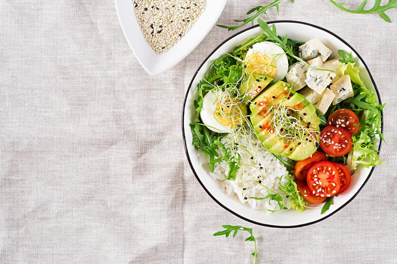 Healthy green vegetarian buddha bowl lunch with eggs, rice, tomato, avocado and blue cheese stock images