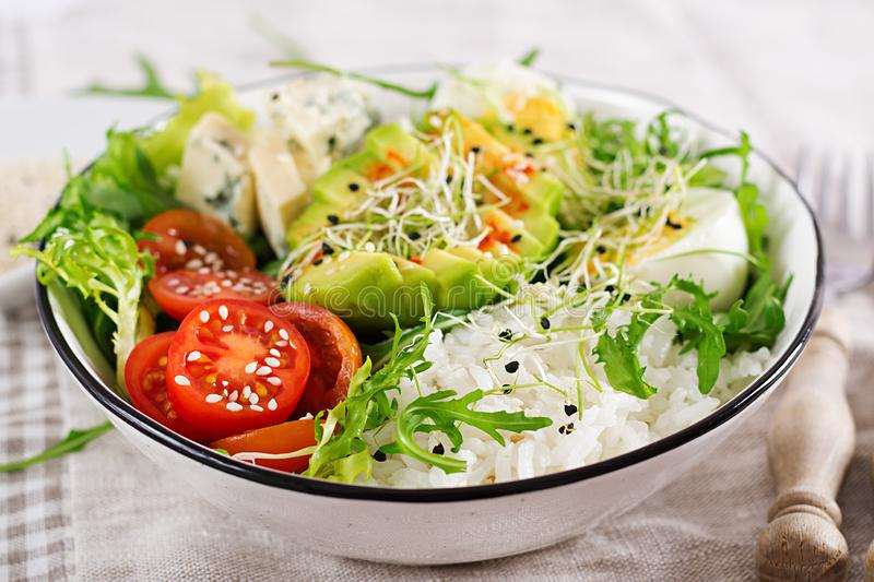 Healthy green vegetarian buddha bowl lunch with eggs, rice, tomato, avocado and blue cheese royalty free stock photo