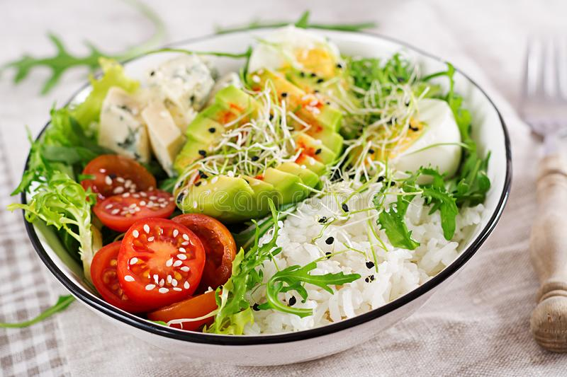 Healthy green vegetarian buddha bowl lunch with eggs, rice, tomato, avocado and blue cheese royalty free stock photography
