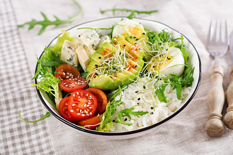 Healthy green vegetarian buddha bowl lunch with eggs, rice, tomato, avocado and blue cheese stock photo