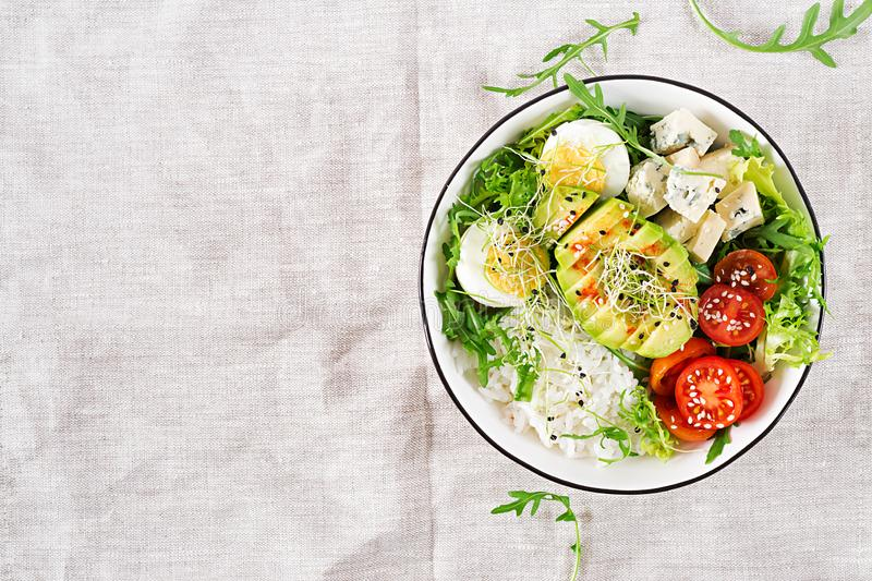 Healthy green vegetarian buddha bowl lunch with eggs, rice, tomato, avocado and blue cheese royalty free stock image