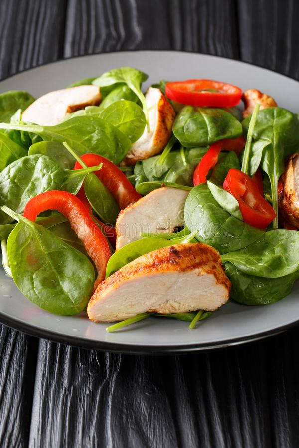 Healthy grilled chicken breast salad with fresh baby spinach and bell peppers closeup on a plate. vertical royalty free stock photography