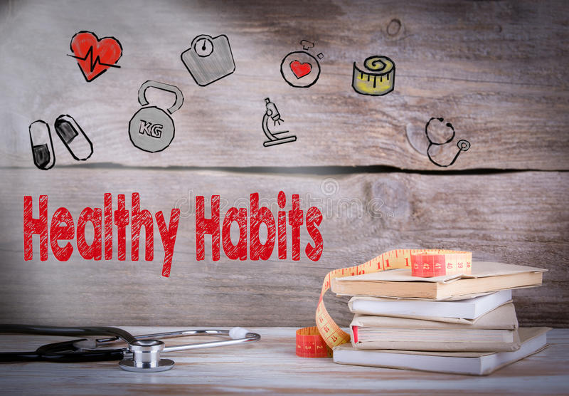 Healthy habits Concept. Stack of books and a stethoscope on a wooden background stock image