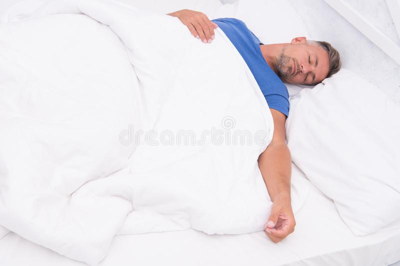 Healthy habits. Man handsome guy lay in bed sleeping. Get enough amount of sleep. Tips sleeping better. Bearded peaceful. Man sleeping face relaxing on pillow royalty free stock photo