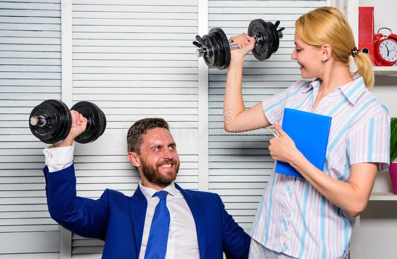 Healthy habits in office. Man and woman raise heavy dumbbells. Strong powerful business strategy. Good job concept. Boss. Healthy habits in office. Man and women royalty free stock photos