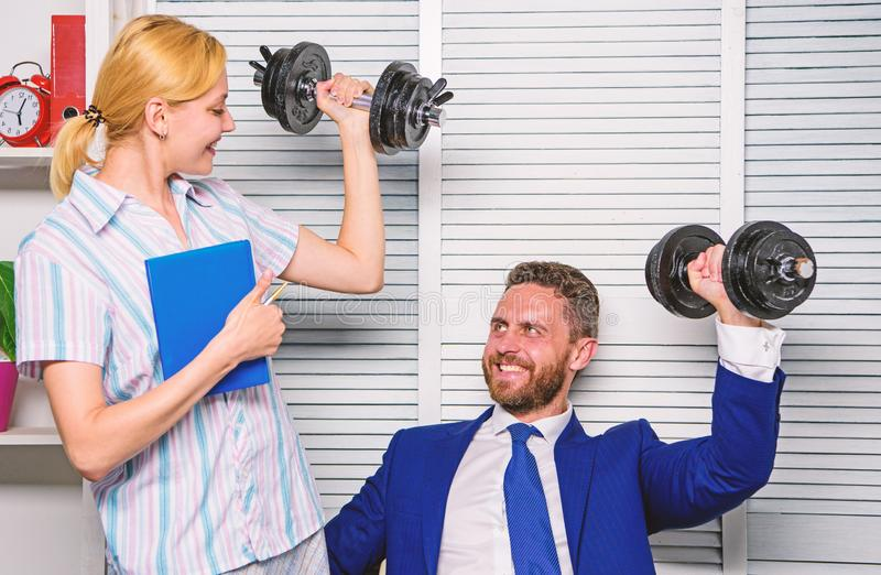 Healthy habits in office. Man and woman raise heavy dumbbells. Strong powerful business strategy. Good job concept. Boss. Healthy habits in office. Man and women royalty free stock images