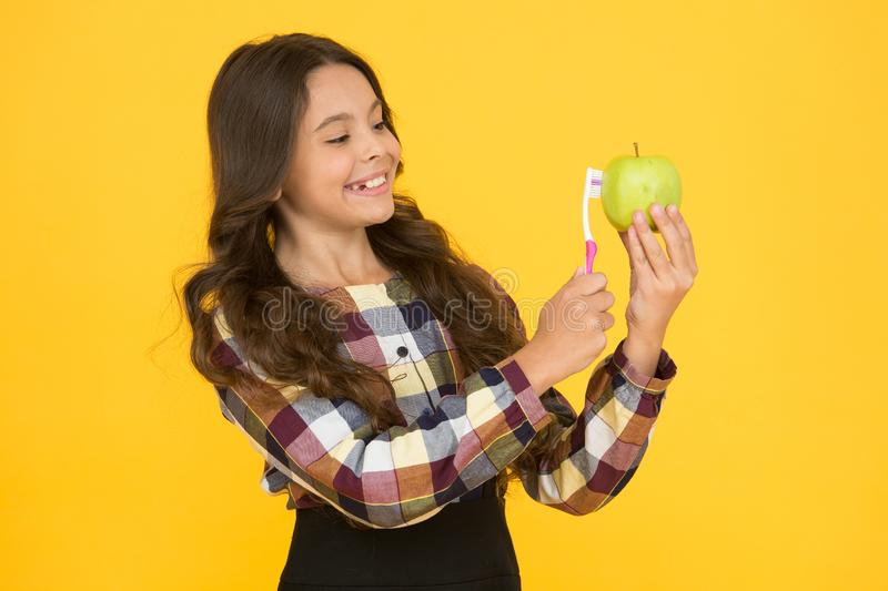 Healthy habits. Small child with healthy smile brush apple. Good oral hygiene. Keep teeth and gums healthy. Tooth. Friendly food. Healthy eating. Dental health stock photo