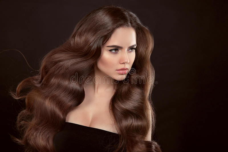 Healthy hair. Wavy hairstyle. Beautiful brunette woman with clean skin and shiny brown straight long hair isolated on black stock photos