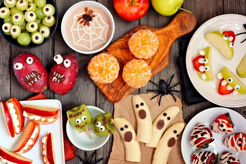 Healthy Halloween fruit treats, top view table scene over a rustic wood background. Healthy Halloween fruit snacks. Selection of fun, spooky treats. Top view royalty free stock photography