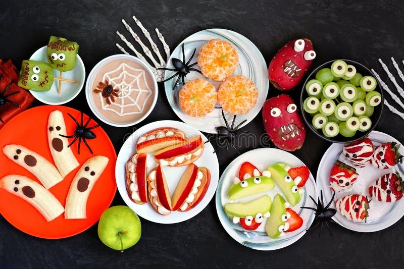 Healthy Halloween fruit treats, top view table scene over a black stone background. Healthy Halloween fruit snacks. Selection of fun, spooky treats. Top view royalty free stock photo
