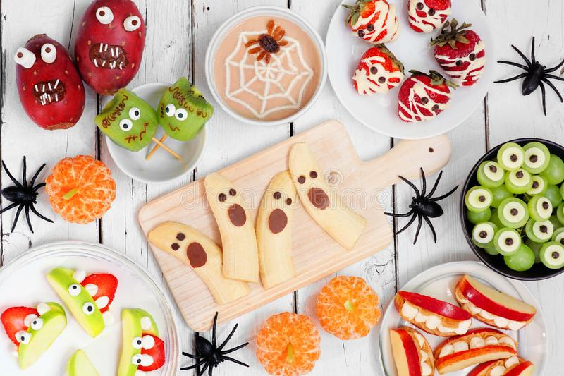 Healthy Halloween fruit treats, top view table scene over a white wood background. Healthy Halloween fruit snacks. Selection of fun, spooky treats. Top view royalty free stock photo