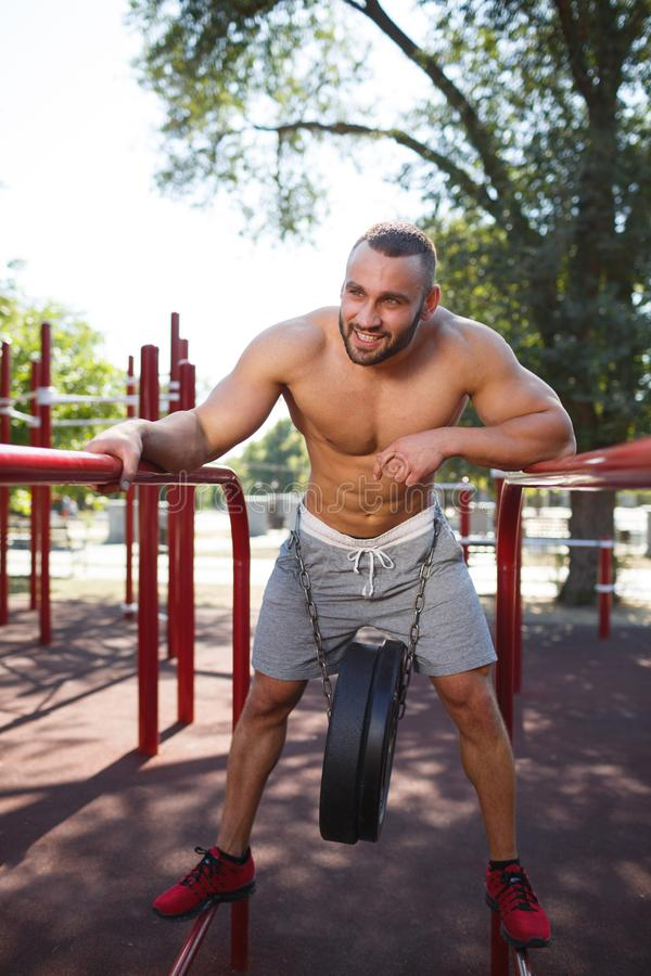 Workout exercise outside. Sports and fitness concept. Healthy handsome and active man with fit muscular body, doing exercises. Sporty athletic male training stock images