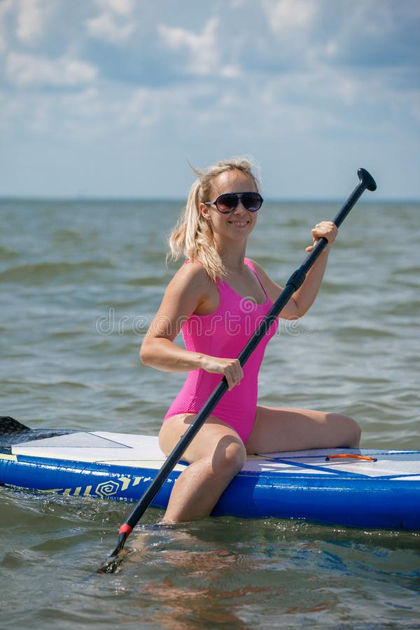 Healthy Happy Athletic Girl In Wetsuit Paddling On Stand Up Paddle SUP, Surfing Board In Sea. Summer Fun, Holidays Travel Vacation. Lifestyle. Recreational royalty free stock photo