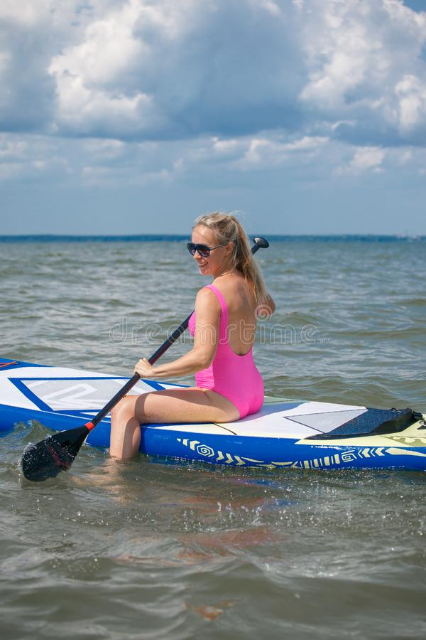 Healthy Happy Athletic Girl In Wetsuit Paddling On Stand Up Paddle SUP, Surfing Board In Sea. Summer Fun, Holidays Travel Vacation. Lifestyle. Recreational stock photography