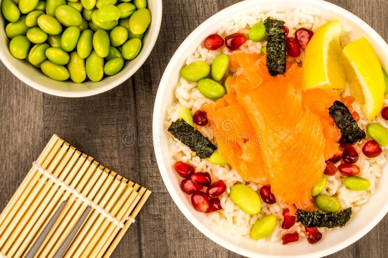 Food bowl of smoked salmon with rice edamame beans seaweed and p. Healthy Hawaiian style poke bowl of smoked salmon with rice edamame beans seaweed and stock images
