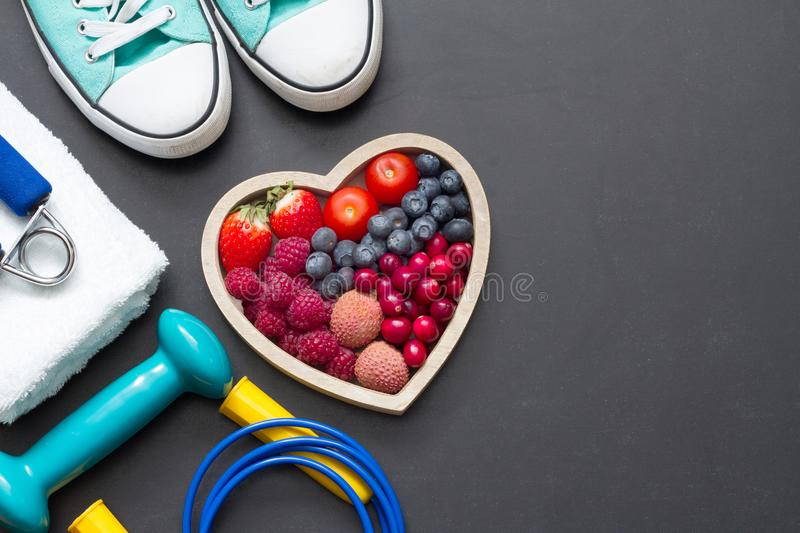 Healthy heart diet and sport gym equipment concept on blackboard royalty free stock image