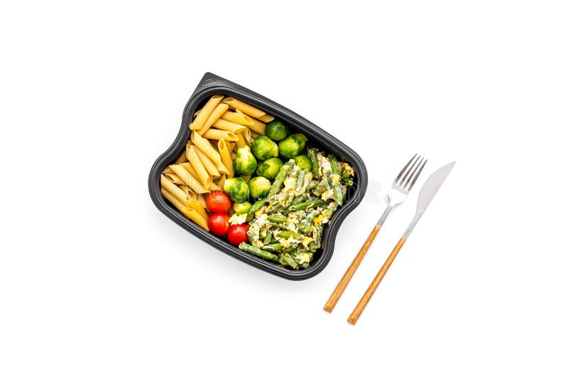 Healthy and hearty lunch for office worker. Vegetables Brussels sprout, cherry tomatoes, knock beans near pasta in royalty free stock photo