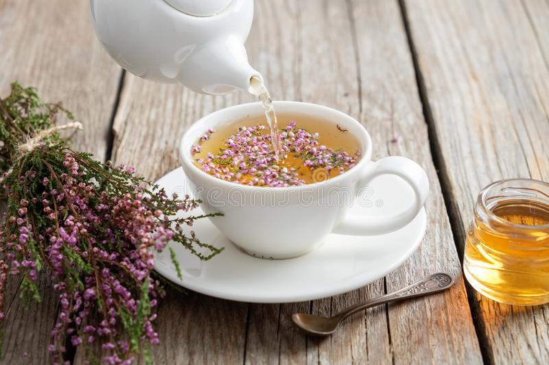 Healthy heather tea poured into white cup. Teapot, honey jar and heather bunch. Healthy heather tea poured into white cup. Teapot, small honey jar and heather royalty free stock photography