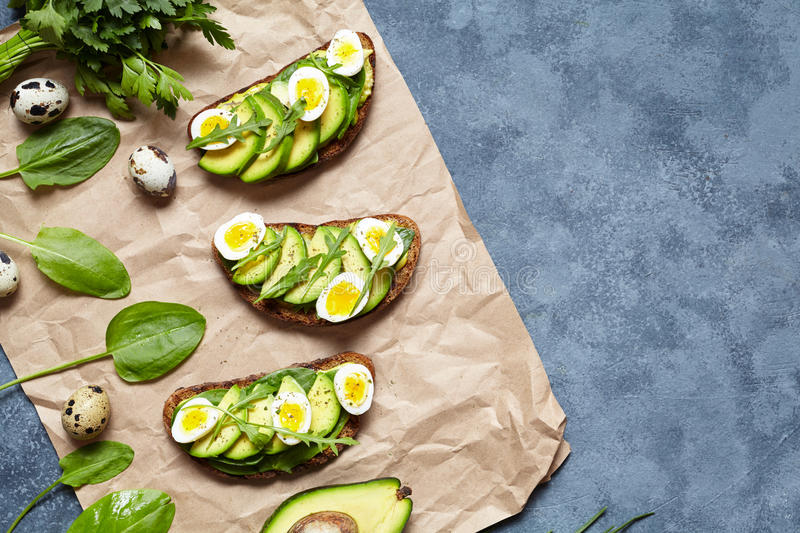 Healthy homemade avocado toast sandwiches with guacamole, slice avocados, spinach, arugula and quail eggs on parchment royalty free stock photography