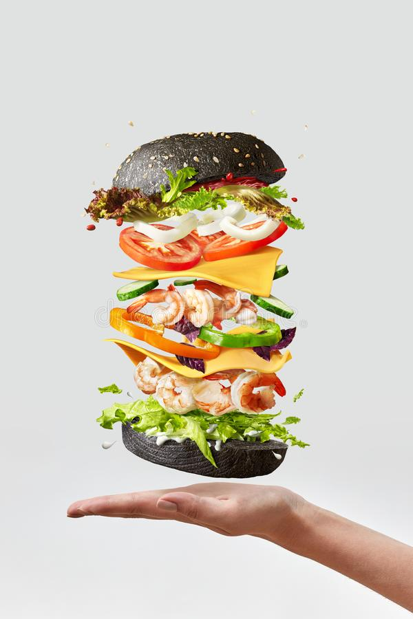 Healthy homemade burger with fresh shrimp and vegetables above the hand on a light background. stock image