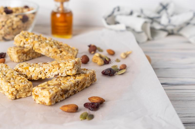 Healthy homemade granola bars with nuts, honey and dried fruit on wooden table stock photography