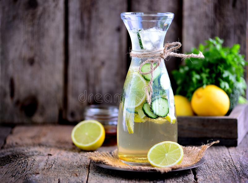 Healthy homemade lemonade made of lime, cucumber and syrup agave with ice. Rustic style, old wooden background. Food stock photos