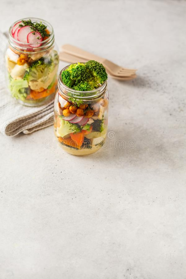 Healthy Homemade Mason Jar Salad with baked vegetables, hummus, stock image